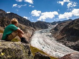 Boy sitting on rock looks at the Kaunertaler glacier Gepatschferner